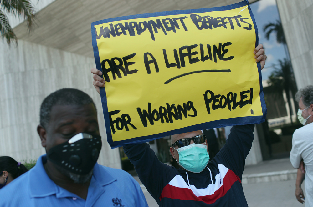 Carlos Ponce joins other demonstrators participating in a protest asking Senators to support the continuation of unemployment benefits on July 16, 2020 in Miami Springs, Florida.